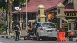 Petugas kepolisian mengamankan mobil yang digunakan terduga teroris setelah serangan di luar markas polisi di Pekanbaru, Riau (16/5). Empat pelaku penyerangan ditembak dan tewas ketika mereka melakukan serangan.  (AFP Photo/Dedy Sutisna)