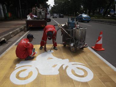 Pekerja mengecat rambu jalur kuning khusus sepeda motor di Jalan Medan Merdeka, Jakarta, Selasa (16/1). Untuk membuat kawasan tersebut tetap tertib, Dishub DKI membuatkan jalur khusus sepeda motor di sepanjang jalan tersebut. (Liputan6.com/Arya Manggala)