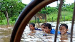 Hujan yang turun sejak Minggu (8/2) lalu, mengakibatkan kawasan perumahan mewah Garaharaya di Tangerang, Banten terendam air setinggi lebih kurang 90 cm. Tampak sejumlah bocah asyik bermain air, Selasa (10/2/2015). (Liputan6.com/Faisal R Syam)