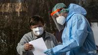 Seorang tentara Ceko yang mengenakan alat pelindung (APD) menunjukkan hasil tes virus corona kepada seorang pasien di kota Chodova Plana, Bohemia barat. (Foto: AFP / Michal Cizek)