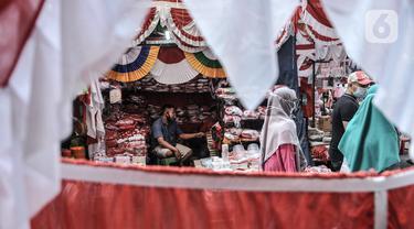 Pedagang menunggu pembeli pernak-pernik Hari Kemerdekaan di Pasar Jatinegara, Jakarta, Minggu (2/8/2020). Menjelang perayaan HUT ke-75 Republik Indonesia, Pasar Jatinegara mulai dipadati warga yang ingin mencari beragam pernak-pernik hiasan kemerdekaan. (merdeka.com/Iqbal Nugroho)