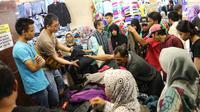 Pedagang melayani pembelinya di Pasar Tanah Abang, Jakarta, Minggu (18/6). Karena ramainya, terlihat di setiap sudut toko para pedagang tengah sibuk melayani para calon pembeli. (Liputan6.com/Immanuel Antonius)