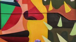 Seorang wanita berada di dekat karya seni Mural di TIM, Cikini, Jakarta, Selasa (11/9). Mural tersebut dibuat untuk mempererat kerjasama antara Pemprov DKI Jakarta dengan Kedutaan Besar Kolombia dalam bidang seni perkotaan. (Liputan6.com/Faizal Fanani)