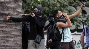 """Demonstran berselfie ketika yang lain menggunakan ketapel menyerang polisi selama bentrok memprotes kebijakan ekonomi pemerintah di Santiago (6/11/2019). Presiden Chile mengatakan """"tidak menyembunyikan apa-apa"""" mengenai tuduhan bahwa polisi membunuh, menyiksa warga sipil. (AFP Photo/Javier Torres)"""