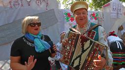 Seorang wanita berfoto dengan musisi yang mengenakan kostum tradisional di Minsk, Belarus, 26 September 2020. Berbagai pameran pertanian digelar di seluruh Belarus untuk merayakan panen musim gugur. (Xinhua/Henadz Zhinkov)