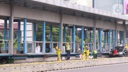 Sejumlah petugas membersihkan puing Halte Bus TransJakarta Tosari yang dirusak saat kericuhan unjuk rasa menolak pengesahan UU Cipta Kerja di Jakarta, Jumat (9/10/2020). Sejumlah fasilitas umum rusak dalam kericuhan yang terjadi Kamis (8/10). (Liputan6.com/Angga Yuniar)