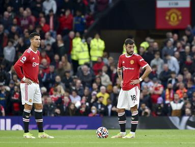 Pemain Manchester United Cristiano Ronaldo (kiri) dan Bruno Fernandes (tengah) bereaksi setelah pemain Liverpool Mohamed Salah mencetak gol ke gawang mereka pada pertandingan Liga Inggris di Old Trafford, Manchester, Inggris, Minggu (24/10/2021). Liverpool menang 5-0. (AP Photo/Rui Vieira)