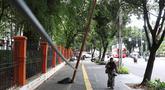 Pejalan kaki melintas di dekat tiang yang miring di Jalan Gedung Kesenian, Jakarta, Jumat (22/2). Keberadaan tiang miring tersebut membahayakan keselamatan pejalan kaki karena kabel yang turut menjuntai hingga ke bawah. (Liputan6.com/Immanuel Antonius)