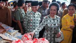 Presiden BJ Habibie didampingi istrinya Ainun Habibie memeriksa bawang putih di pasar murah yang didirikan di Taman Monumen Nasional, Jakarta, 9 Januari 1999. Habibie meninggal setelah mendapat perawatan intensif selama beberapa hari terakhir di RSPAD Gatot Subroto Jakarta Pusat. (AFP Photo/Kompas)