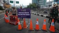 Petugas melakukan penjagaan di kawasan yang ditutup saat penyekatan di ruas jalan Mampang Prapatan, Jakarta, Kamis (15/7/2021). Mampang menjadi salah satu jalan yang masuk dalam penyekatan baru pada Pemberlakuan Pembatasan Kegiatan Masyarakat (PPKM) darurat di Ibu Kota. (merdeka.com/Imam Buhori)