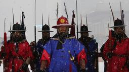 Penjaga istana mengenakan seragam militer tradisional berdiri selama hujan salju di Istana Gyeongbok di Seoul, Korea Selatan (13/12). Istana Gyeongbok aslinya didirikan tahun 1394 oleh Jeong do jeon, seorang arsitek.  (AP Photo/Ahn Young-joon)