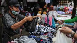 Seorang pedagang menggunakan kantong plastik di Kawasan Pasar Jatinegara, Jakarta, Selasa (30/6/2020). Mulai 1 Juli 2020 penggunaan kantong plastik sekali pakai dilarang di mal, toko swalayan, dan pasar tradisional di DKI Jakarta. (Liputan6.com/Faizal Fanani)