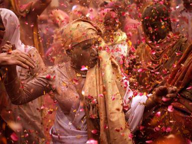 Para janda menari dan saling melempar serbuk berwarna dan kembang saat mengikuti tradisi perayaan Holi di Vrindavan, Uttar Pradesh, India (21/3). Holi merupakan salah satu festival perayaan awal musim semi terbesar di India. (REUTERS/Anindito Mukherjee)
