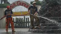 Petugas Diskar Kabupaten Bandung Barat turut membantu membersihkan sisa abu vulkanik di kawasan wisata Gunung Tangkuban Parahu, Minggu (28/7/2019). (Liputan6.com/Huyogo Simbolon)
