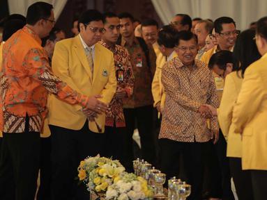 Wakil Presiden Jusuf Kalla (tengah) didampingi Ketum Golkar Airlangga Hartarto saat menghadiri penutupan Munaslub Golkar di Jakarta, Rabu (20/12). Jusuf Kalla mengenakan batik berwarna emas saat menghadiri acara tersebut. (Liputan6.com/Faizal Fanani)