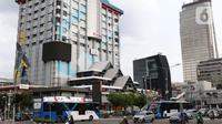 Sejumlah kendaraan melintas di depan pusat perbelanjaan Sarinah, Jakarta, Jumat (3/4/2020). Pemerintah menetapkan Pembatasan Sosial Berskala Besar dengan membatasi kegiatan tertentu penduduk di wilayah yang diduga terinfeksi COVID-19. (Liputan6.com/Helmi Fithriansyah)