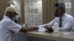 Pekerja melayani nasabah di kantor cabang Bank Syariah Indonesia, Jakarta Selasa (2/2/2021). Pada 27 Januari 2021, BSI telah mendapatkan persetujuan dari OJK ditandai dengan keluarnya Salinan Keputusan Dewan Komisioner OJK Nomor 4/KDK.03/2021. (Liputan6.com/Johan Tallo)