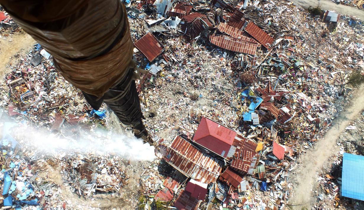 Penyemprotan cairan disinfektan di kawasan terdampak likuifaksi di Perumnas Petobo dan Balaroa, Palu, Sulawesi Tengah, Kamis (18/10). Penyemprotan dilakukan untuk mengantisipasi penyebaran penyakit. (Muhammad Rifki/AFP)