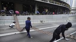 Demonstran menyeret pagar untuk menghalangi jalan selama protes di distrik keuangan di Hong Kong (14/11/2019). Warga Hong Kong mengalami hari keempat kemacetan lalu lintas dan gangguan angkutan massal ketika pengunjuk rasa menutup beberapa jalan utama dan jaringan kereta api.  (AP Photo/Vincent Yu)