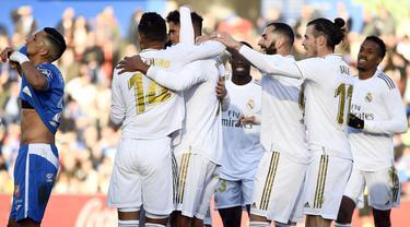 Para pemain Real Madrid merayakan gol yang dicetak Raphael Varane ke gawang Getafe pada laga La Liga Spanyol di Stadion Col Alfonso Perez, Getafe, Sabtu (4/1). Getafe kalah 0-3 dari Madrid. (AFP/Oscar Del Pozo)