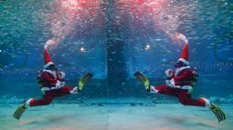 Seorang penyelam yang mengenakan kostum sinterklas tampil di antara kawanan ikan sarden di Coex Aquarium, Seoul, Selasa (18/12). Coex Aquarium merupakan dunia laut yang terbesar di Korea Selatan dan rumah bagi 40.000 makhluk laut (AP Photo/Ahn Young-joon)