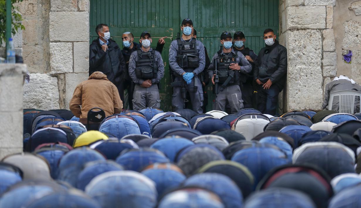 Pasukan keamanan Israel berjaga saat umat muslim Palestina melaksanakan salat Idul Fitri di luar Kompleks Masjidil Aqsa, Yerusalem, Minggu (24/5/2020). Masjidil Aqsa akan dibuka kembali setelah Idul Fitri karena pandemi virus corona COVID-19. (AHMAD GHARABLI/AFP)