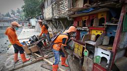 Petugas menghancurkan kandang burung merpati saat penertiban unggas di bantaran Kali Ciliwung, Senen, Jakarta, Rabu (18/11). Penertiban dilakukan untuk mencegah penyebaran virus flu burung. (Liputan6.com/Immanuel Antonius)