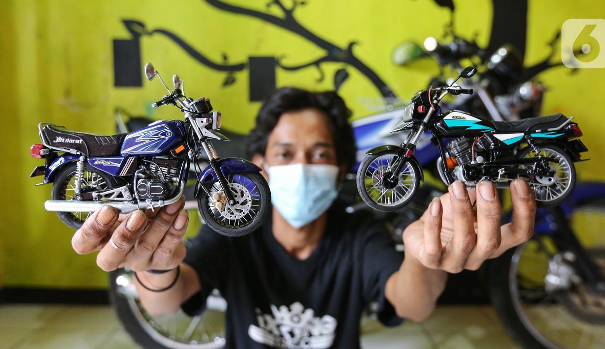 Pengrajin Wawang Kurniawan, menunjukkan dua miniatur motor RX-King dan GL-Pro di Kampung Dukuh, Serua, Tangerang Selatan, Sabtu (17/10/2020). Miniatur motor yang terbuat dari barang bekas paralon, kaleng minuman mulai digeluti sejak tahun 2018. (Liputan6.com/Fery Pradolo)