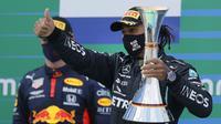 Pembalap Mercedes Lewis Hamilton memegang trofi saat merayakan kemenangannya pada F1 GP Eifel di Nuerburgring, Nuerburg, Jerman, Minggu (11/10/2020). Hamilton dengan 91 kemenangannya menyamai legenda F1 Michael Schumacher. (Ronald Wittek, Pool via AP)