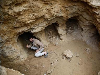 Abdel-Karim Cafran, warga Palestina Beit Hanun mengumpulkan pecahan tembikar di sebuah pemakaman yang baru ditemukan di kebun rumahnya di kota di Jalur Gaza utara, (26/1). (AFP Photo/Mohammed Abed)