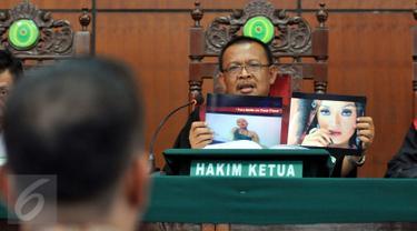 Sidang lanjutan dugaan pelanggaran hak cipta oleh PT Vista Pratama kembali digelar di Pengadilan Negeri Jakarta Utara pada Selasa (18/8/2015). Hakim Ketua tampak memperlihatkan barang bukti foto dalam sidang tersebut. (Liputan6.com/Panji Diksana)