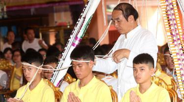 Pelatih tim sepak bola remaja Thailand, Ekkapol Janthawong (tengah) bersama anak asuhnya mengikuti ritual di Distrik Mae Sai, Chiang Rai, Kamis (19/7). Ritual ini diyakini memperpanjang hidup serta membersihkan mereka dari bahaya. (AP Photo/Sakchai Lalit)