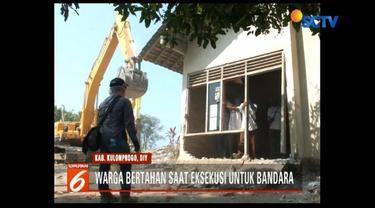 Tolak pengosongan lahan, seorang warga gigit petugas saat rumahnya digusur untuk pembangunan bandara di Kulonprogo, Yogyakarta.