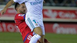 Aksi pemain Real Madrid, Lucas Vazquez (kanan) melewati adangan pemain Numancia, Grego pada laga Copa Del Rey di Nuevo Estadio Los Pajaritos stadium, Soria, (4/1/2018). Madrid menang 3-0. (AFP/Cesar Manso)