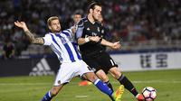Pemain Real Madrid, Gareth Bale, berusaha melewati pemain Real Sociedad, Inigo Martinez. Bale berhasil mencetak dua gol kemenangan Los Blancos yang dibukukannya pada menit ke-2 dan 90+4. (AP/Alvaro Barrientos)
