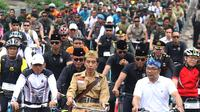 Presiden Joko Widodo (tengah) didampingi Gubernur Jawa Barat Ridwan Kamil (kanan) saat mengikuti Bandung Lautan Sepeda, Sabtu (10/11). Kegiatan yang diadakan oleh Kodam III/Siliwangi ini dalam rangka memperingati Hari Pahlawan. (Liputan6.com/Angga Yuniar)