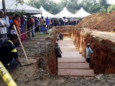 Sejumlah orang menyaksikan pemakaman massal jenazah yang di duga etnis Rohingya di Alor Setar, Malaysia, Senin (22/6/2015).  21 dari 106 jenazah tak dikenal yang ditemukan bulan lalu dimakamkan hari ini. (Reuters/Olivia Harris)