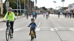 Seorang wanita dan anak kecil mengendarai sepeda di jalan-jalan bebas kendaraan bermotor selama acara CicLAvia di Culver City, Los Angeles, Minggu (3/3). Di Los Angeles, car free day disebut juga CicLAvia. (Chris Delmas/AFP)