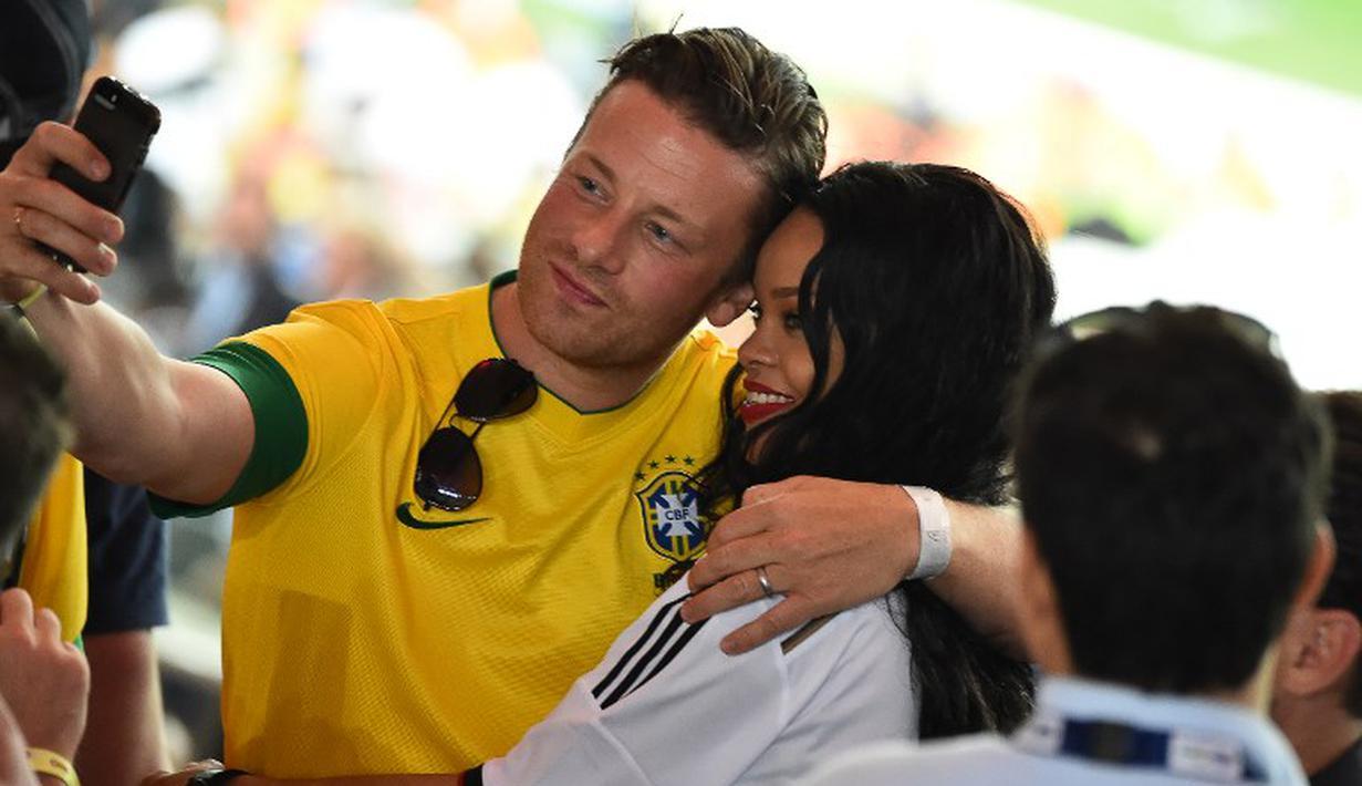 Chef  Jamie Oliver berpose selfie dengan penyanyi Umbrella ini setelah kemenangan Jerman dalam final Piala Dunia FIFA antara Jerman dan Argentina  di Stadion Maracana, Rio de Janeiro, (13/7/14), (AFP PHOTO / Gabriel Bouys).