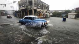 Sebuah mobil tua Amerika Serikat melewati jalan yang banjir di Havana, Kuba, 30 Juni 2021. Hujan deras dan selokan yang tidak berfungsi menyebabkan banjir di jalan-jalan di Havana. (YAMIL LAGE/AFP)