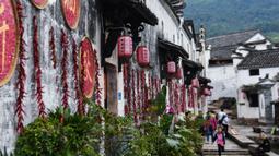 Sejumlah wisatawan mengunjungi desa kuno Xinye di Kota Jiande, Provinsi Zhejiang, China timur, pada 15 Oktober 2020. Dihiasi tanaman beraneka warna, desa kuno tersebut menarik minat banyak pengunjung. (Xinhua/Xu Yu)