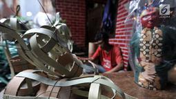 Andri saat menyelesaikan pembuatan kerangka ondel-ondel di Jakarta, Selasa (19/3). Dalam sehari Andri mampu memproduksi sekitar 50-70 buah ondel-ondel yang dibanderol dengan harga Rp 30 ribu-Rp 50 ribu per buah. (merdeka.com/ Iqbal S. Nugroho)