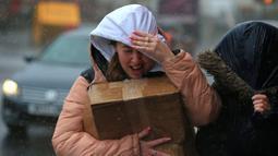Seorang wanita berusaha melindungi dirinya dari angin kencang dan hujan di Sheffield, Inggris utara (9/2/2020). Badai Ciara diperkirakan akan mengganggu penerbangan, kereta api dan laut dan membatalkan acara olahraga, memutus tenaga listrik dan merusak properti. (AFP Photo/Lindsey Parnaby)