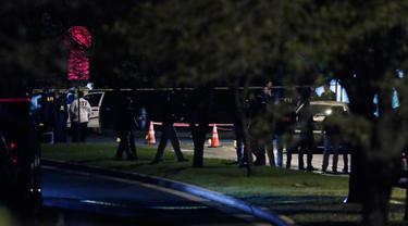 Petugas menyelidiki di dekat daerah ledakan Minggu malam  di Austin, Texas (18/3). Sedikitnya dua orang terluka akibat insiden ini setelah beberapa hari tiga bom paket membunuh dua orang di kota yang sama pada awal bulan ini. (AP Photo/Eric Gay)