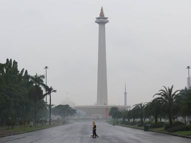 Petugas menyapu sampah yang tercecer di kawasan Monas, Jakarta, Senin (3/11). Kesigapan petugas kebersihan pasca reuni 212 membuat kawasan tersebut kembali bersih meskipun sehari sebelumnya dipenuhi ratusan ribu orang. (Liputan6.com/Immanuel Antonius)