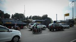 Pengendara melintas dekat deretan kendaraan taktis milik Brimob yang disiagakan di sekitar bundaran Patung Kuda, Jakarta, Jumat (28/7). Kendaraan taktis disiapkan untuk mengamankan aksi 287 yang digelar Presidium Alumni 212. (Liputan6.com/Faizal Fanani)