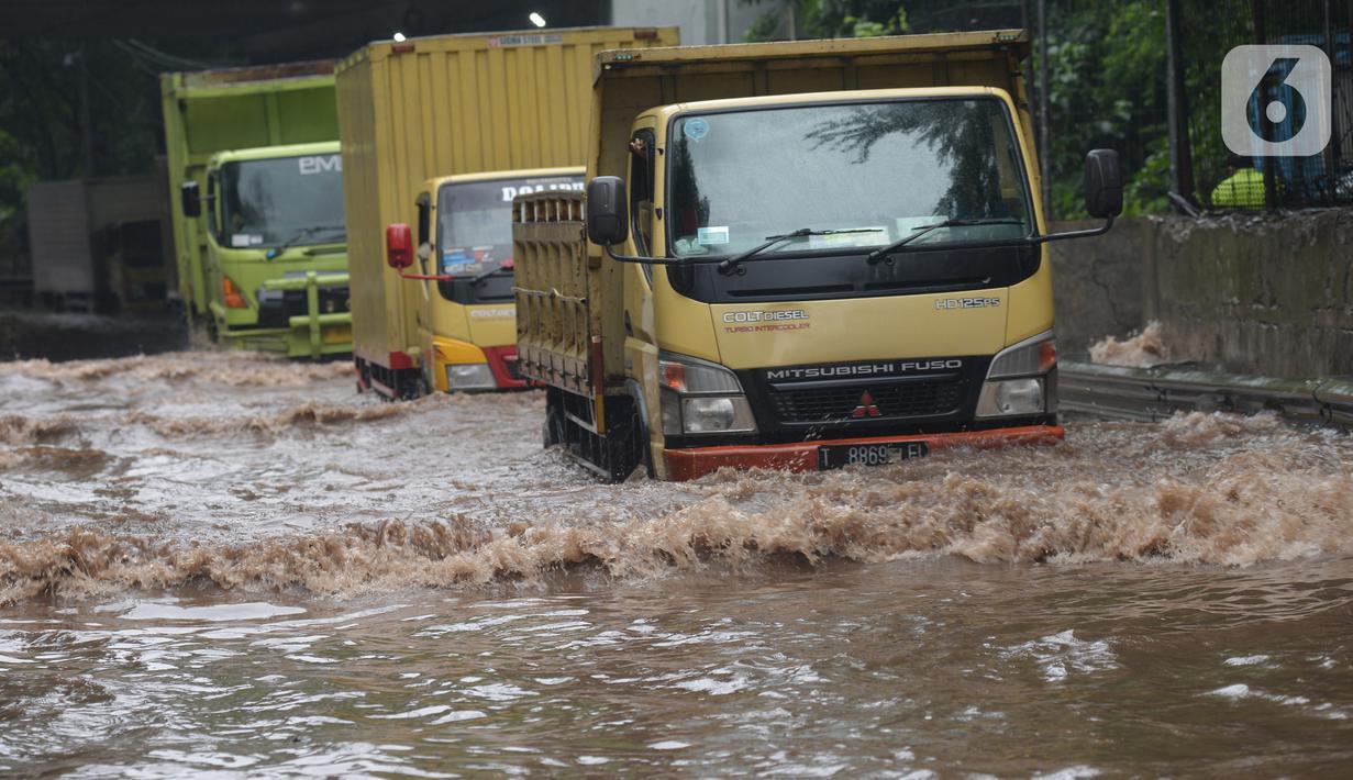 Sejumlah truk melewati banjir yang merendam terowongan di Cawang, Jakarta, Jumat (19/2/2021). Hujan yang turun sejak semalam membuat sejumlah jalanan di Ibu Kota tergenang banjir dengan ketinggian sekitar 30-50 cm. (merdeka.com/Imam Buhori)