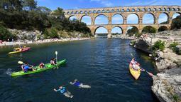 Wisatawan bermain kayak di dekat Pont du Gard atau Jembatan Gard di Vers-Pont-du-Gard, Prancis, Rabu (21/8/2019). Pont du Gard merupakan jembatan saluran air dari batu yang terdiri dari tiga tingkatan. (Pascal GUYOT/AFP)