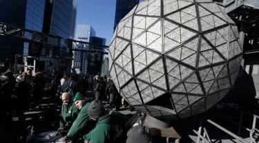 Pekerja menyelesaikan pemasangan kristal berbentuk segitiga pada bola kristal di atas One Times Square, New York, Amerika Serikat, Rabu (27/12). Nantinya, bola kristal tersebut akan diluncurkan ke bawah pada malam tahun baru. (AP/Seth Wenig)