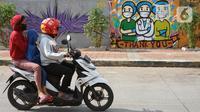 Pengendara sepeda motor melintas di depan mural bertema pandemi virus corona COVID-19 di kawasan Sunter, Jakarta, Selasa (2/6/2020). Mural tersebut dibuat sebagai wujud dukungan terhadap tenaga medis serta masyarakat agar tetap semangat menghadapi pandemi COVID-19. (Liputan6.com/Immanuel Antonius)